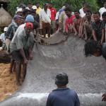 Fischer beim Einholen des Netzes am Strand von Induruwa